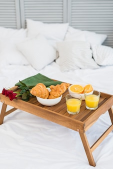 Food and flowers on breakfast table on bed