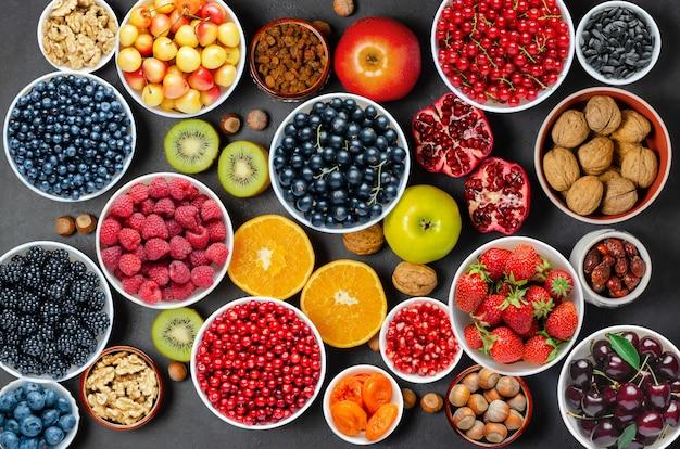 健康的な食事のための食品:ベリー、フルーツ、ナッツ、ドライフルーツ。黒のコンクリートの背景。