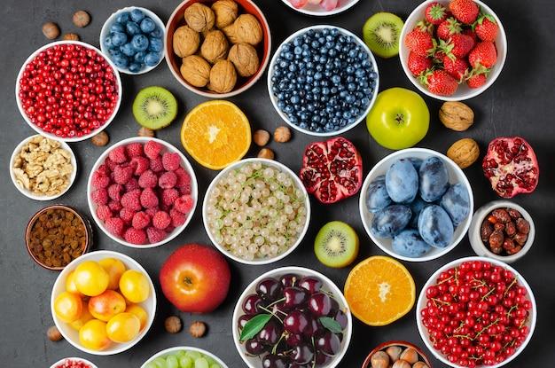 健康的な食事のための食品:ベリー、フルーツ、ナッツ、ドライフルーツ。黒のコンクリートの背景。 Premium写真