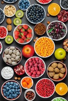 健康的な食事のための食品:ベリー、果物、ナッツ、ドライフルーツ。黒のコンクリートの背景。