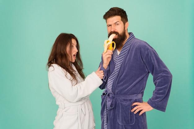 健康のための食べ物健康的な朝食カップル眠そうな顔家庭服はバナナを食べる恋にカップル