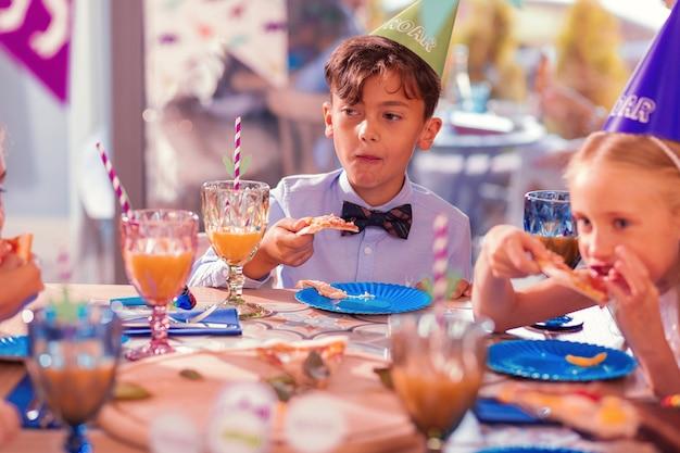 子供のための食べ物。パーティーハットをかぶって、静かにピザを食べている思いやりのある黒髪の少年