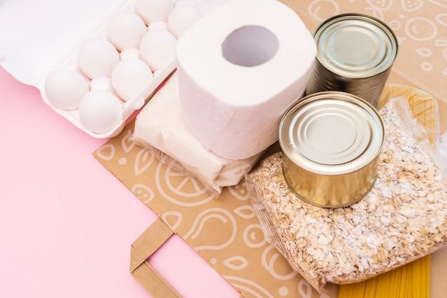 Пища для карантинной изоляции период лежал на желтом пространстве с копией пространства. яйца, макароны, бобы, туалетная бумага, яблоко и некоторые селекционные продукты.
