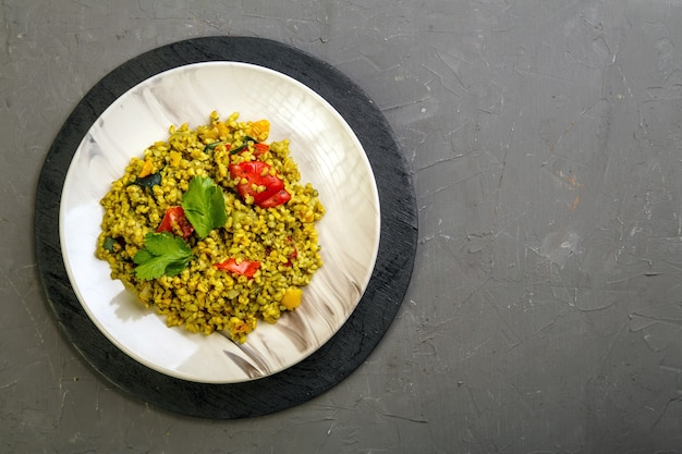 Еда для сухура в пост булгура рамадана с овощами в тарелке на сером фоне. горизонтальное фото