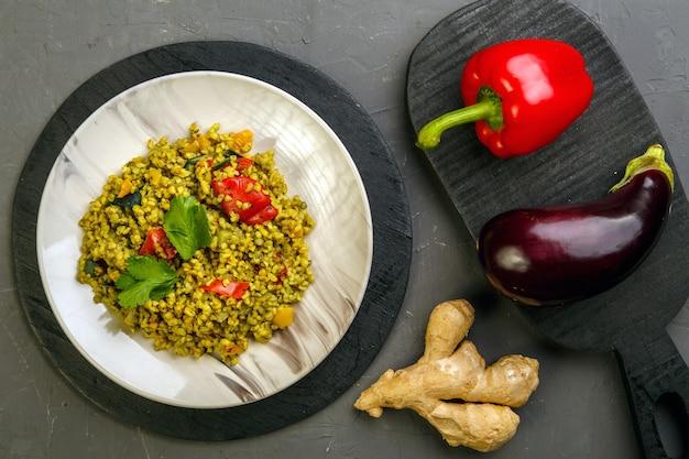 ボード上の野菜の近くの灰色の背景のプレートに野菜を入れたラマダンブルガーポストのスフールの食べ物。横の写真