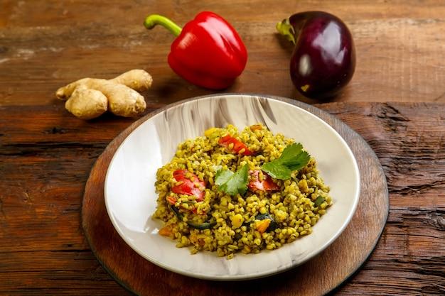 Еда для сухура в пост булгура рамадана с овощами в тарелке на деревянном столе рядом с овощами на доске. горизонтальное фото