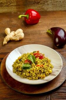 Еда для сухура в пост булгура рамадана с овощами в тарелке на деревянном столе рядом с овощами на доске. вертикальное фото