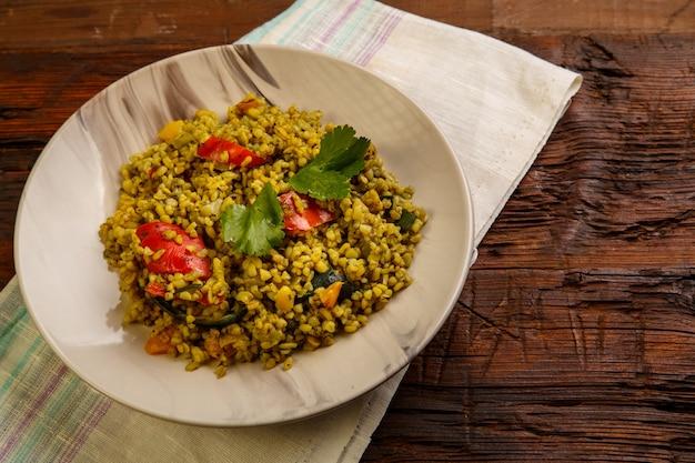 Еда для сухура в пост булгура рамадана с овощами в тарелке на деревянном столе на салфетке. горизонтальное фото