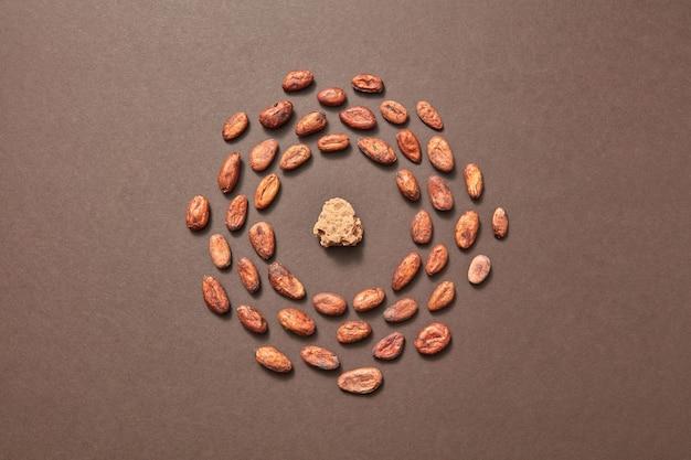 Пищевая рамка из свежих сухих натуральных какао-бобов с частью какао-масла посередине на коричневом фоне, место для текста. плоская планировка. сухие ингредиенты для изготовления темного шоколада.