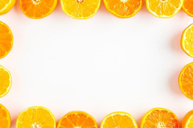 Food frame of halves of mandarin orange on white background
