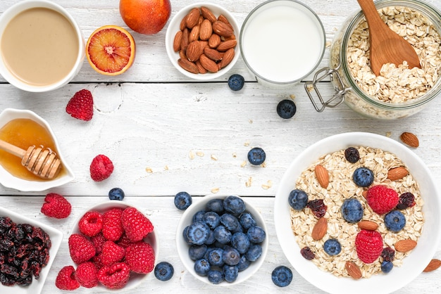 Food frame made of breakfast ingredient. muesli, fruits, berries, cappuccino, nony, milk and nuts. healthy food