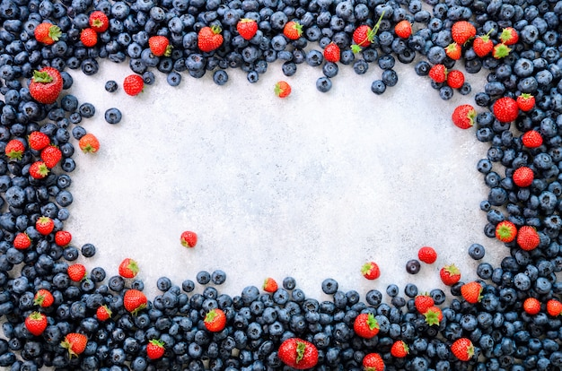 Food frame with mix of strawberry, blueberry. vegan and vegetarian concept. summer berries background