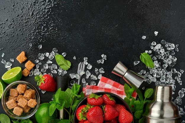 Свежие пищевые ингредиенты для приготовления лимонада, детокс-воды или коктейля. клубника, лайм, мята, базилик, тростниковый сахар, кубики льда и шейкер на черном каменном или бетонном фоне. вид сверху.
