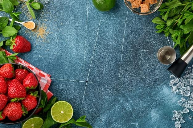 Свежие пищевые ингредиенты для приготовления лимонада, детокс-воды или коктейля. клубника, лайм, мята, базилик, тростниковый сахар, кубики льда и шейкер на темно-синем каменном или бетонном фоне. вид сверху