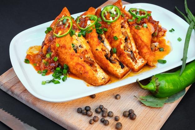 テーブルの上の皿にキノコとトマトのクローズアップと食品揚げ豆腐