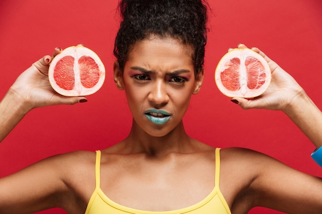 Food frowning afro american woman with trendy makeup holding two halves of fresh ripe grapefruit in both hands isolated, over red wall