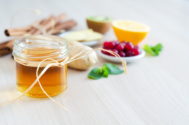 Food for healthy and immunity boosting with vitamin c, honey, lemon, cranberries, kiwi, cinnamon, ginger root on light wood