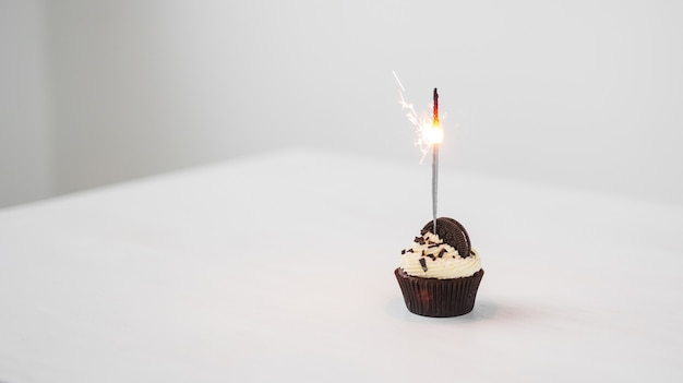 Food and holiday concept - birthday cupcake with sparkler over white background with copy space.