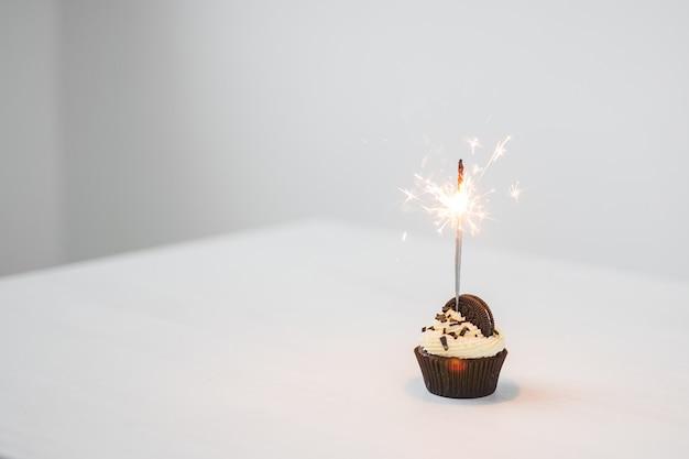 食べ物、休日、お誕生日おめでとう、パン屋、デザートのコンセプト-コピースペースと白いテーブルに線香花火とおいしいカップケーキ