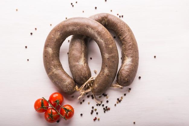 食べ物、馬肉、おいしいコンセプト-トマトとコショウのスライスソーセージ