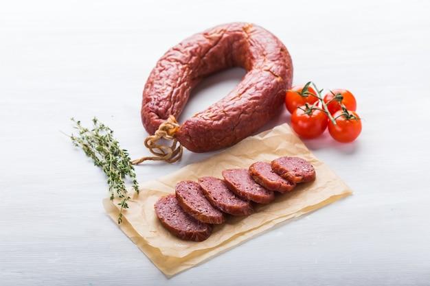 Еда, конина и вкусная концепция - вид сверху нарезанной колбасы с помидорами и перцем.