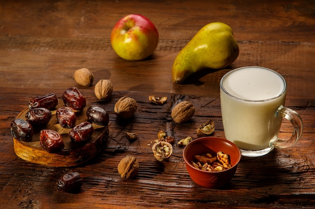 Food for iftar in holy ramadan on a wooden table dates, fruits and ayran. horizontal photo