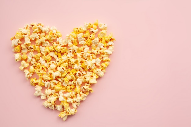 Food. image of the heart forms from popcorn. delicious popcorn on pink. cinema.