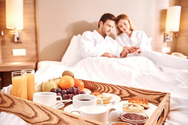 ベッドでの食事。カップルは一緒にホテルの部屋のベッドで抱きしめています。ラブストーリー。朝食のクローズアップ