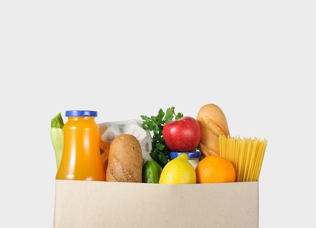 Еда в бумажном пакете на сером фоне. концепция доставки еды.