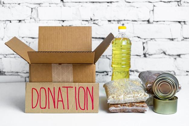 段ボール募金箱の食べ物。検疫隔離期間中の必須商品の危機防止在庫。フードデリバリー、コロナウイルス。