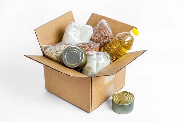 段ボール募金箱、白い背景で隔離の食品。検疫隔離期間中の必須商品の危機防止在庫。フードデリバリー、コロナウイルス。食糧不足。