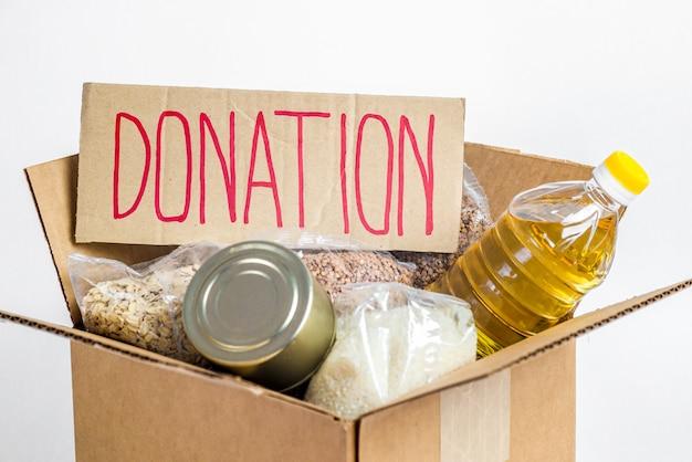 段ボール募金箱、白い背景で隔離の食品。検疫隔離期間中の必須商品の危機防止在庫。フードデリバリー、コロナウイルス。