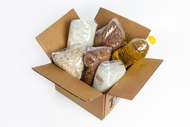 段ボール募金箱、白い背景で隔離の食品。検疫隔離期間中の必須商品の危機防止在庫。