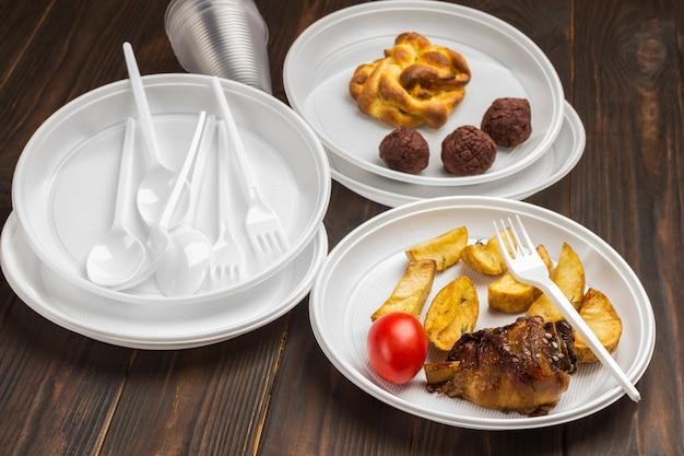 일회용 흰색 플라스틱 식기에 담긴 음식. 환경 보호. 문제는 재활용입니다. 나무 테이블. 평면도
