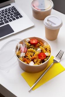 Еда в отнимающих коробках на белом столе с ноутбуком