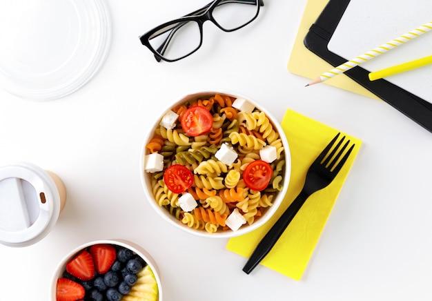 Еда в отняв коробки на белом столе с блокнотом