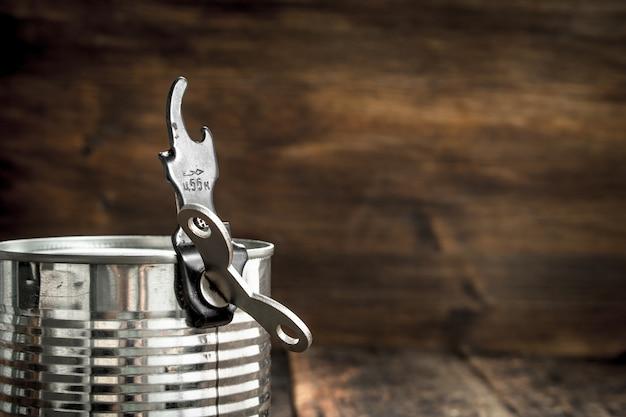 木製のテーブルにオープナー付きのブリキ缶の食品。