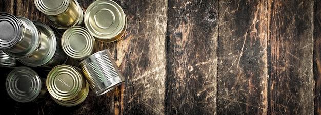 缶詰の食品。木製の背景に。
