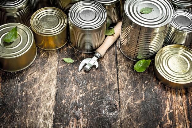 オープナー付きのブリキ缶の食品。木製の背景に。