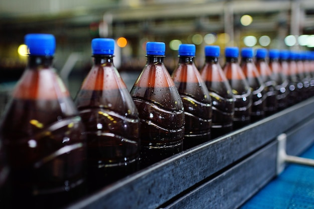 Food industrial production of beer. plastic beer bottles on a conveyor belt against the background of a brewery.
