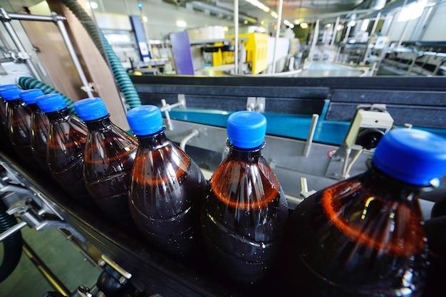 Пищевое промышленное производство пива. пластиковые пивные бутылки на конвейерной ленте на фоне пивоварни.