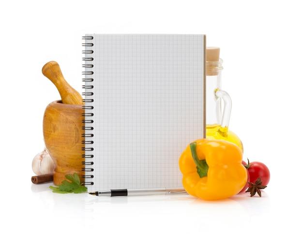 Пищевые ингредиенты и книга рецептов на белом