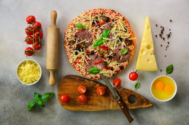 Food ingredients for italian pizza, cherry tomatoes, flour, cheese, basil, rolling pin, board, knife, spices on light grey concrete. top view, copy space