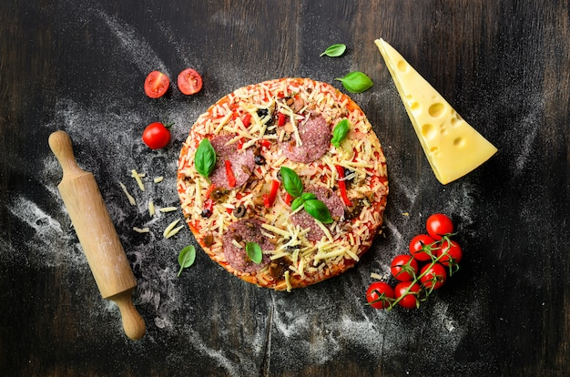 Food ingredients for italian pizza, cherry tomatoes, flour, cheese, basil, rolling pin, spices on dark. top view, copy space