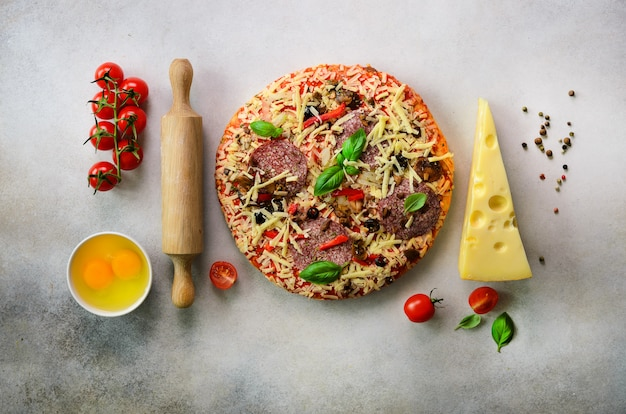 Food ingredients for italian pizza, cherry tomatoes, flour, cheese, basil, rolling pin, spices on light grey.