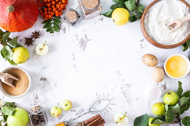 Food ingredients for making autumn pumpkin pie on white stone background. homemade baking concept. frame