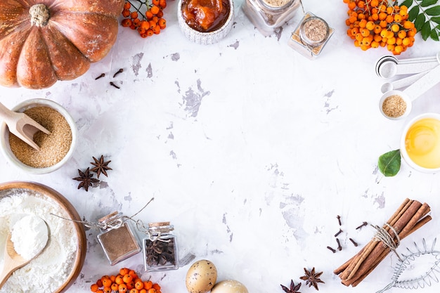 Food ingredients for making autumn pumpkin pie on white stone background. homemade baking concept. top view. copy space