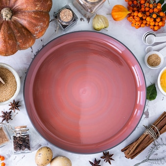 Food ingredients for making autumn pumpkin pie on white stone background. homemade baking concept.