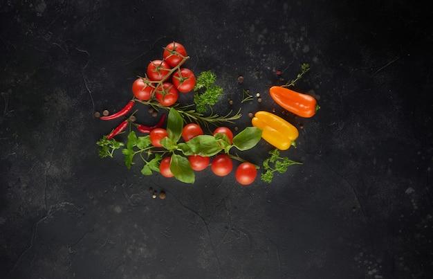 食品成分。黒のスレートの背景にスパイス、ハーブ、野菜。コピースペースのある上面図