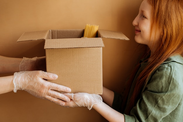 Food is collected in a donation box and passed from hand to hand.